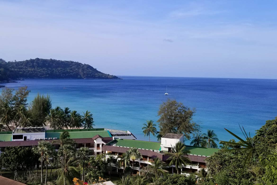 A overlook from a hotel balcony at the blue ocean waters and architecture of Phuket, Thailand