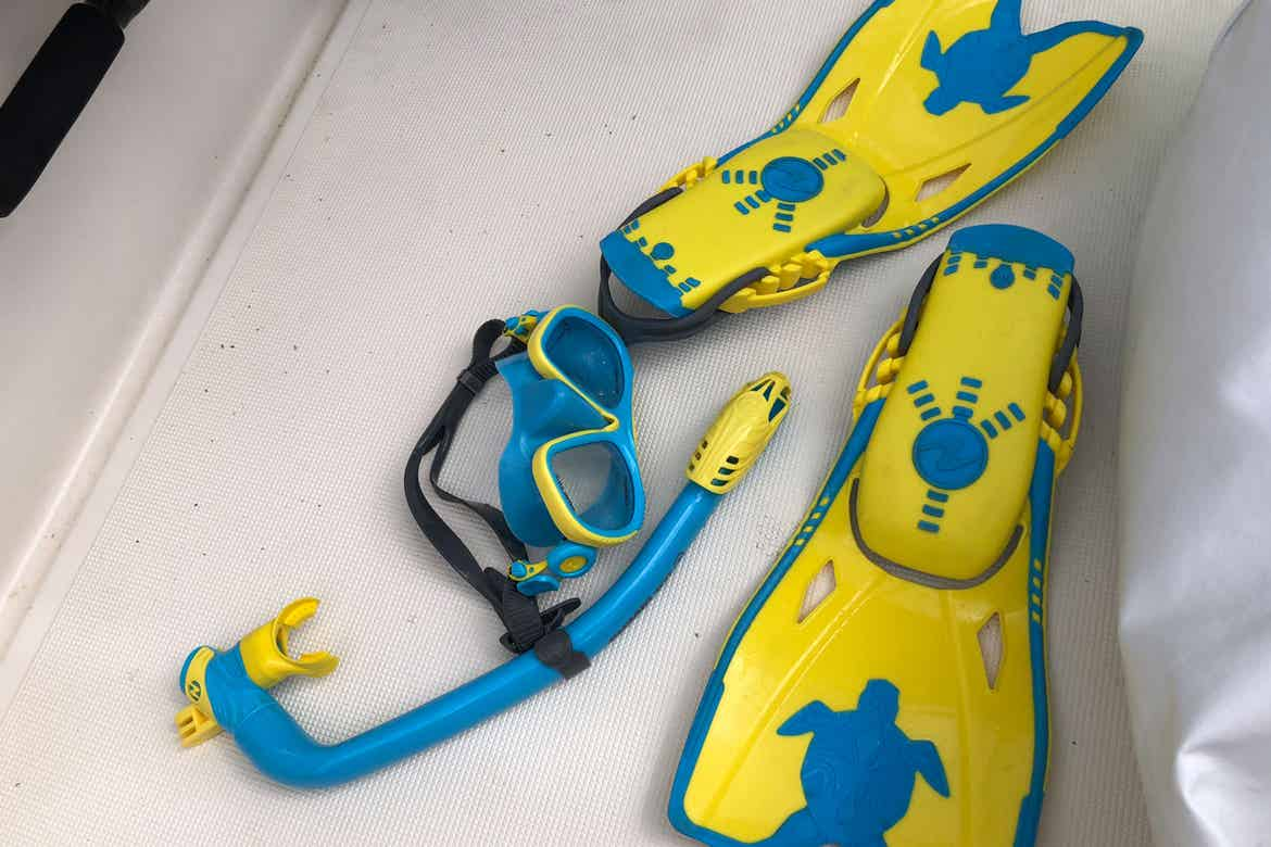 A pair of yellow and blue swimming fins and matching snorkel gear placed on the floor of a boat.