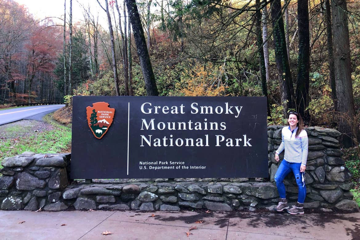Featured Contributor, Jennifer C. Harmon, poses with a sign that reads, 'Great Smoky Mountains National Park' wearing a white pullover and jeans.