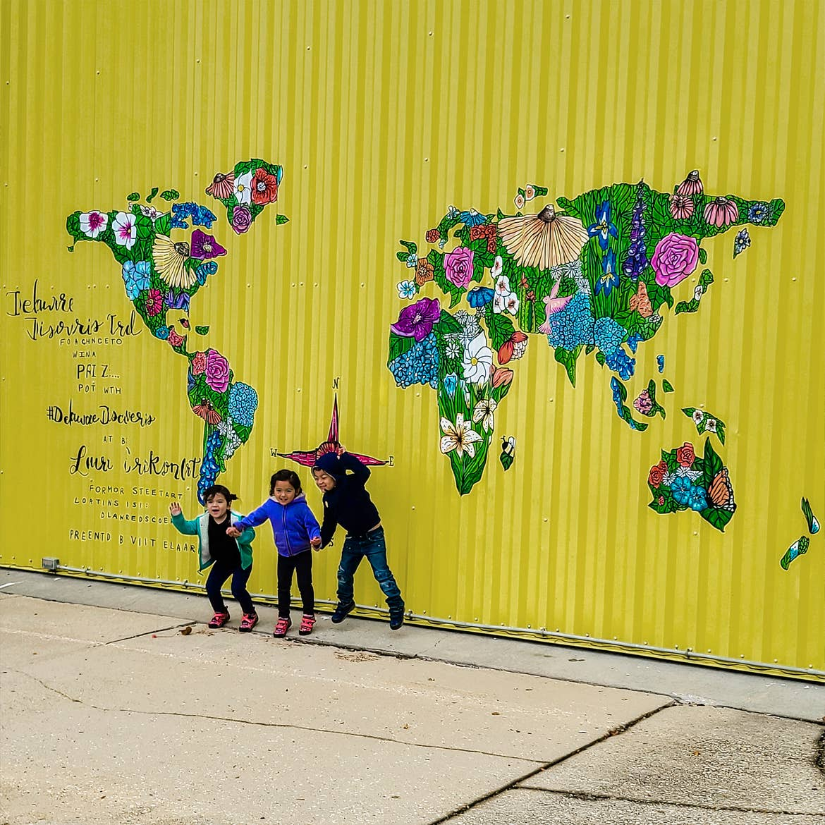 Three Asian Pacific Islander toddlers (left to right: Two girls and a boy) wear long-sleeve shirts and pants in front of a galvanized yellow wall with a mural of the world map with floral patterns.