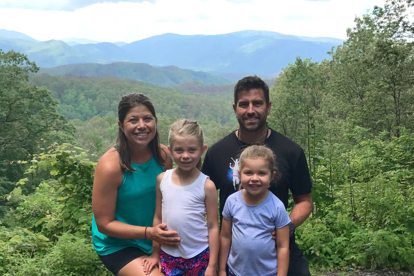 Author, Chris Johnston (far-left), stands in front of a range of trees at the Great Smoky Mountains with her husband, Josh (far-right), and daughters, Kyndall (front-left), and Kyler (front-right).