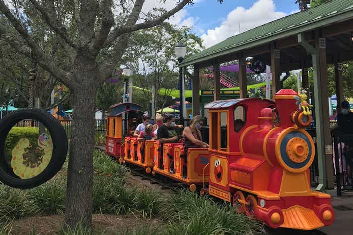 Guests are seated on Elmo's Choo Choo Train wearing masks and skipping rows to maintain social distancing.