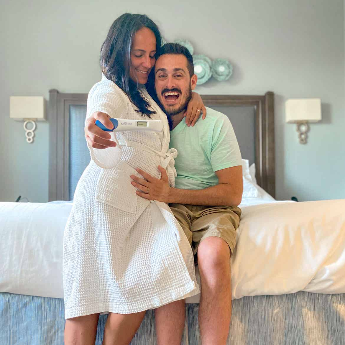 Featured Contributor, Danny Pitaluga (right) smiles as he hugs his wife, Val (left), as she holds a positive pregnancy test in a white robe.