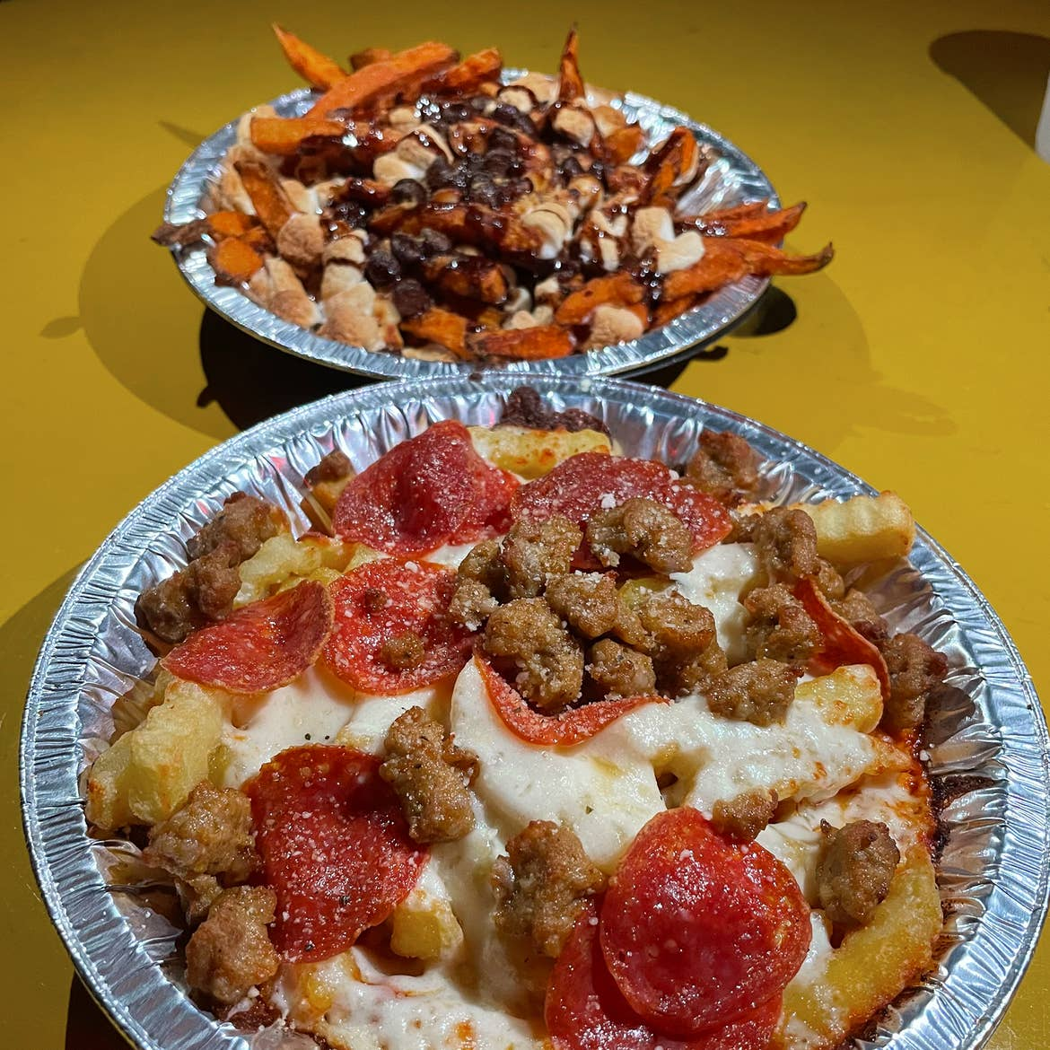 French fries with various toppings on a yellow table.