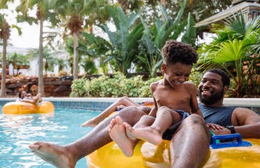 A young boy and his father sit on an orange inner tube in the lazy river in River Island at our Orange Lake resort located in Orlando, FL.