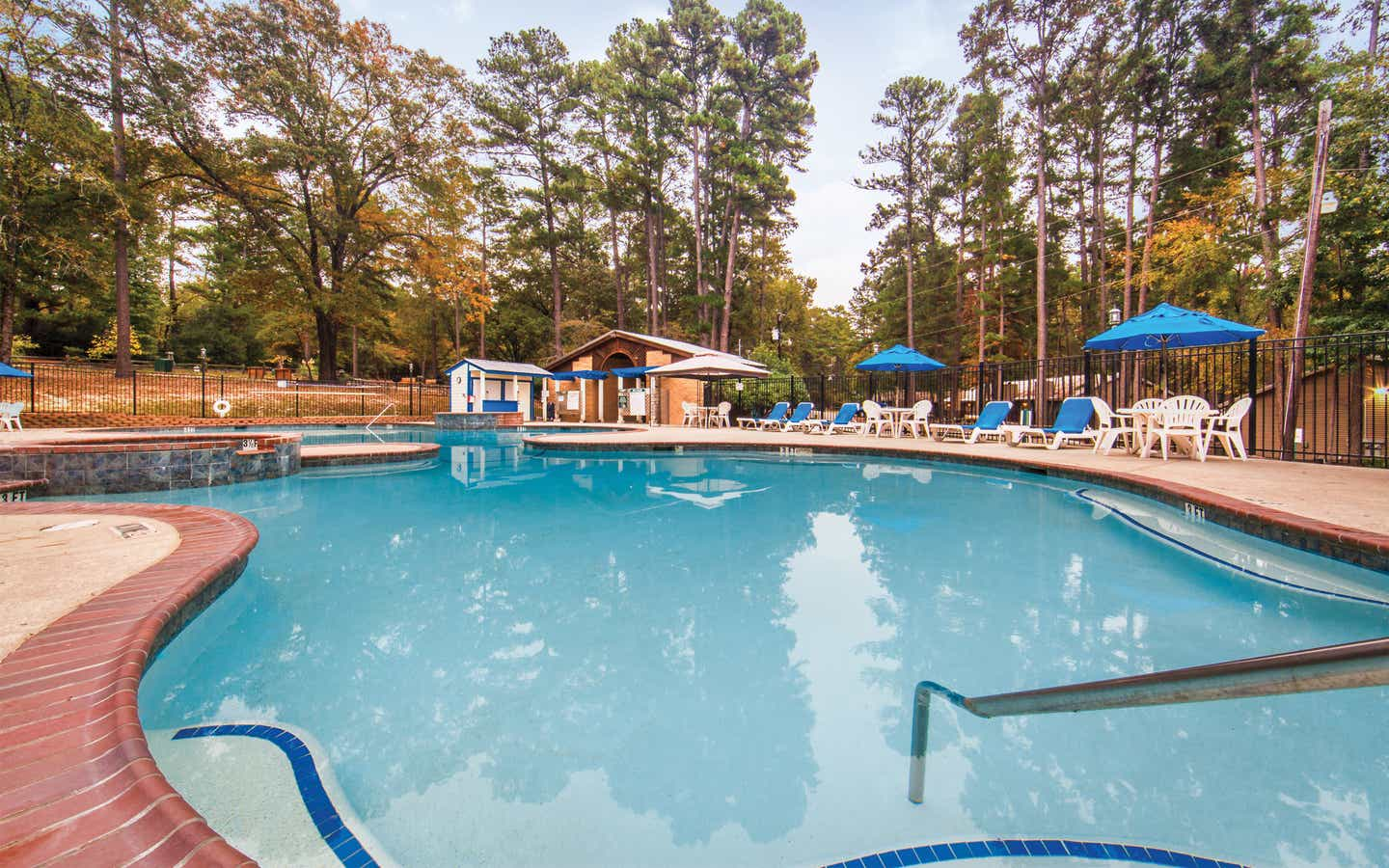 Outdoor pool with sun umbrellas at Holly Lake Resort in Texas.