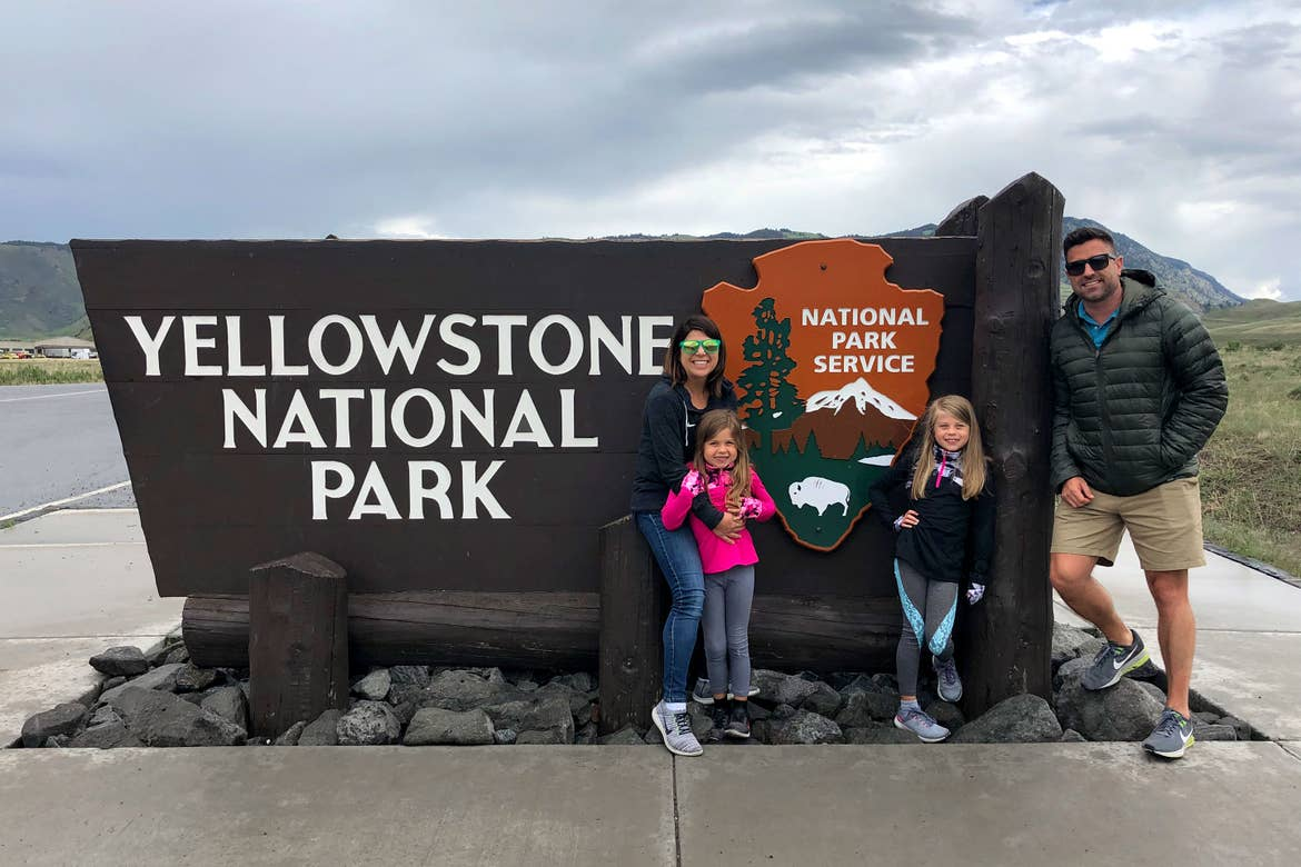 Author, Chris Johnston (far-left), with her husband, Josh (far-right), and daughters, Kyndall (front-right), and Kyler (front-left) pose with a sign that reads, 'Yellowstone National Park, National Park Service.'