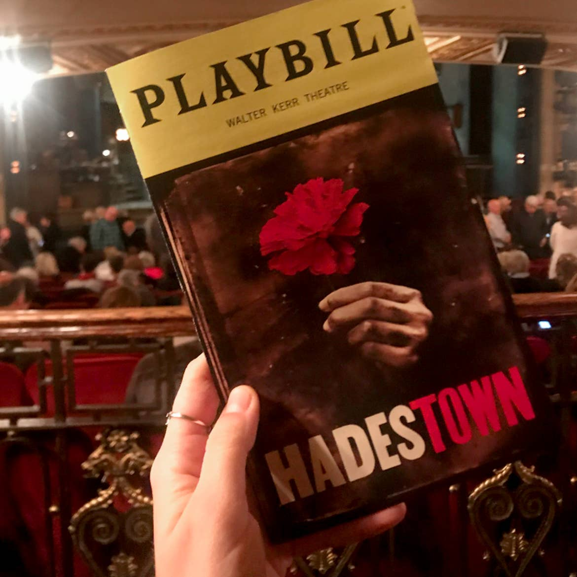 A Playbill booklet for the production of 'Hadestown' is held by a caucasian woman's hand inside of a theater.