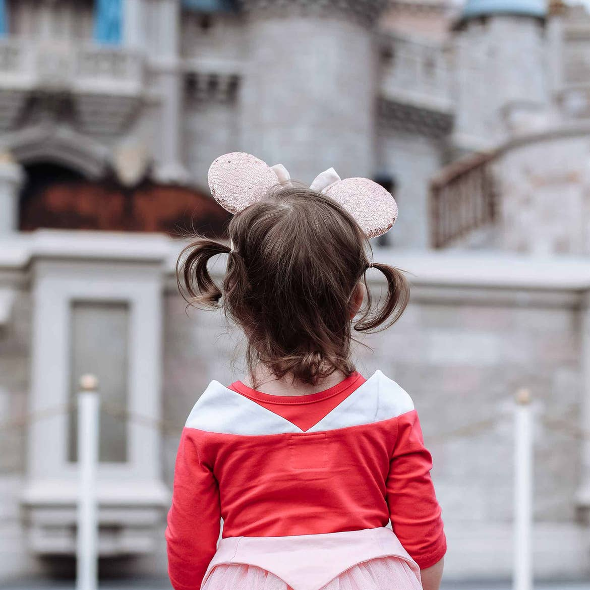 Poppy Bleu stands in front of Cinderella's Castle at Magic Kingdom Park at Walt Disney World® Resort wearing a pink Aurora dress and sparkly Minnie ears.