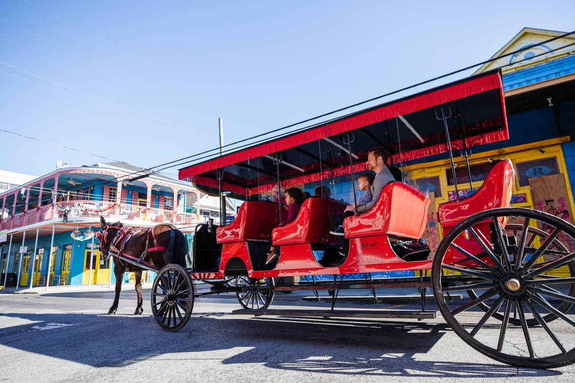 Featured Contributor, Sally Butan of @butanclan and her family  ride a red horse-drawn carriage through the streets of New Orleans, Louisiana.