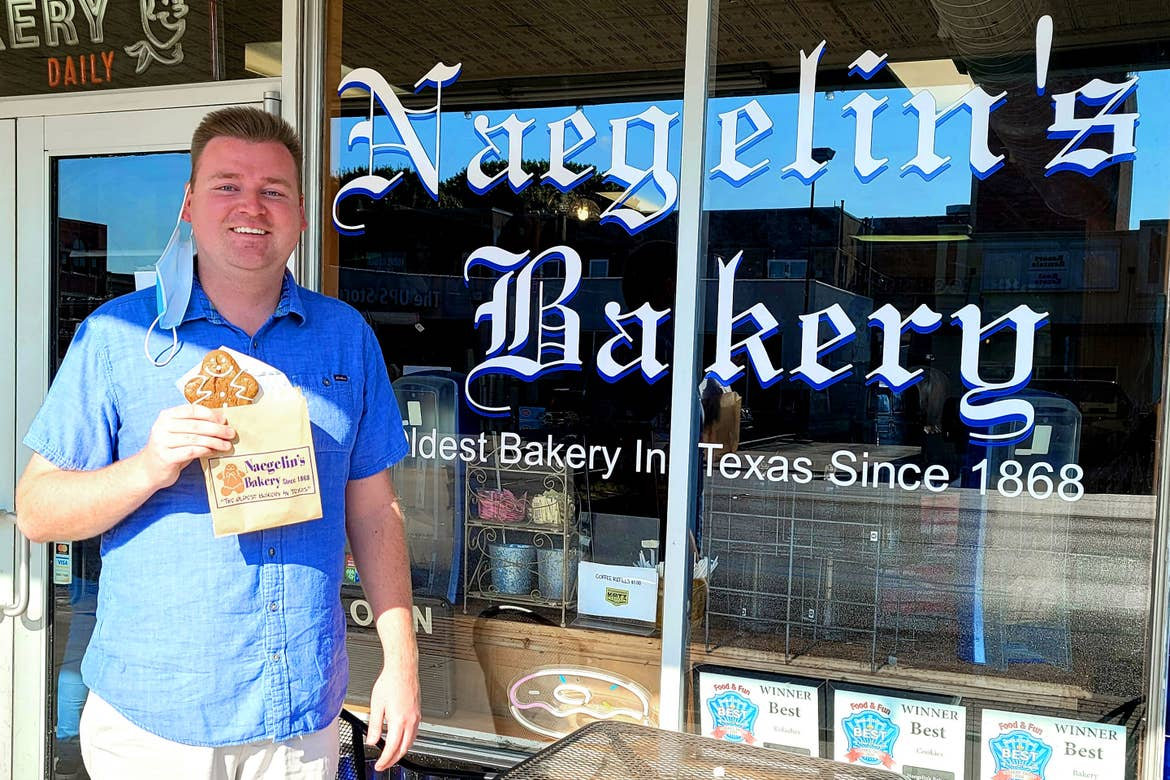 Author, Chris Harms, stands in a blue button-up shirt holding a gingerbread in front of the Naeglin's Bakery signpainting on the front window.