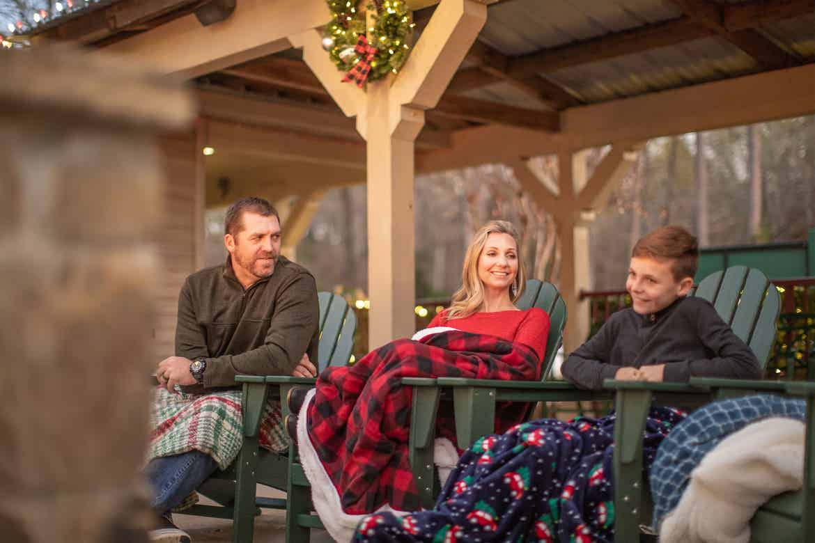 Author, Amanda Nall (middle) sits outdoors with her husband (left) and son (right) wearing cozy throw blankets outdoors.