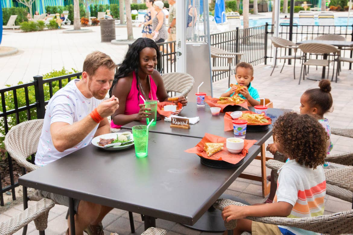 Featured Contributor, Sally Butan (back-left) and her family of five enjoy some beverages at a table at Breezes at our Orange Lake resort located near Orlando, FL.