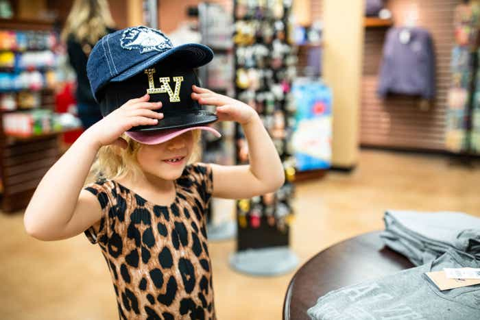 Tinsley Haby shops in the marketplace of our Desert Club Resort located in Las Vegas, Nevada wearing several black baseball hats that read, 'LV.'