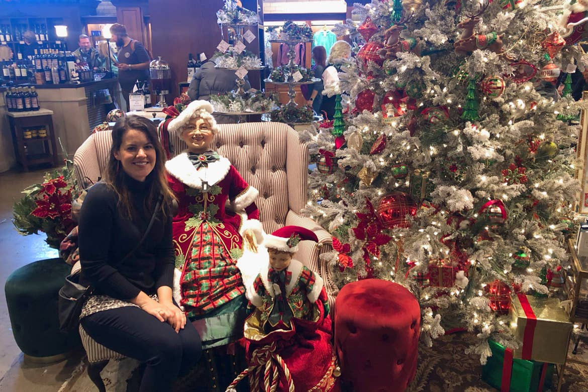 Author, Jenn C. Harmon, wears a black sweater seated near a Mrs. Claus doll near a decorated Christmas tree and other home decor items at the local Christmas Shoppe.