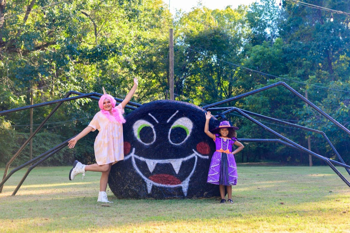 Two girls wear halloween costumes near a hay bail painted to look like a spider outdoors.