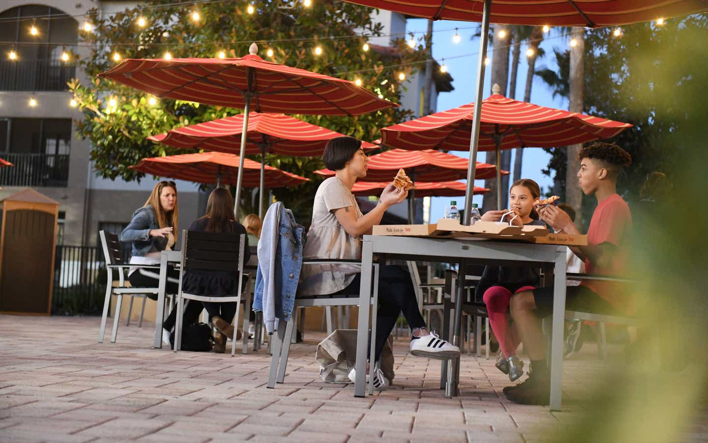 A group of people eating outside of Paisan Pizzeria at Orange Lake Resort near Orlando, Florida.