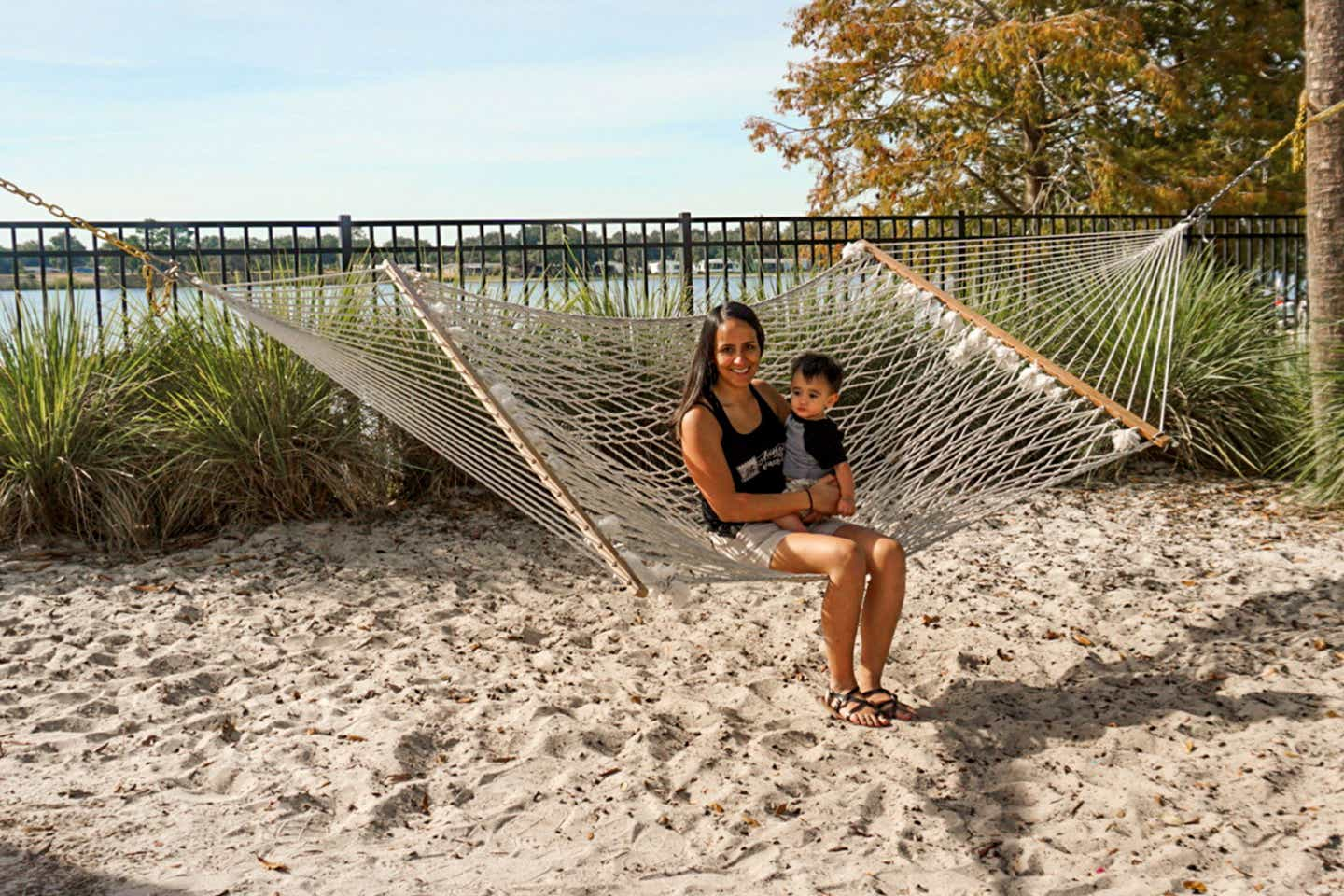 Author, Danny Pitaluga's wife, Val (left), and son, Joey (right), sit on a hammock near a waterfront at our Orange Lake Resort in Orlando, Florida.