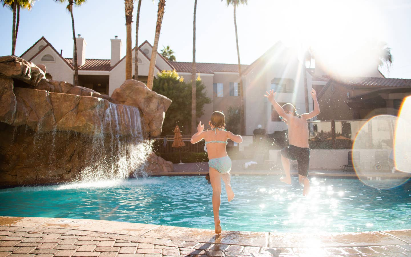 Two children jumping in outdoor pool with waterfall at Desert Club Resort in Las Vegas, Nevada.