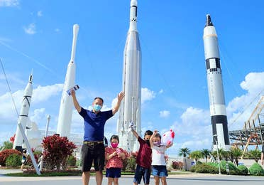 Featured Contributor, Angelica Kajiwara's husband and three children run pose in front of a 'Rocket Playground' located at the Kennedy Space Center™ Visitor Complex.