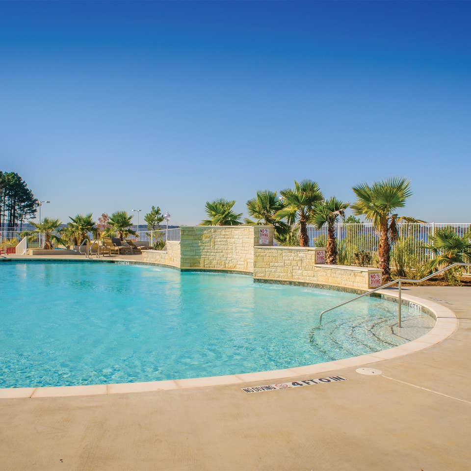 Outdoor pool surrounded by palm trees at Villages Resort in Flint, Texas.