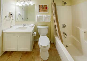 Bathroom with vanity, toilet, and tub in a two bedroom presidential villa at Oak n' Spruce Resort in South Lee, Massachusetts
