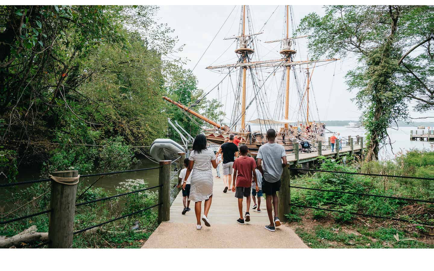 A family walks towards the Susan Constant ship at Jamestown Settlement in Williamsburg, Virginia.