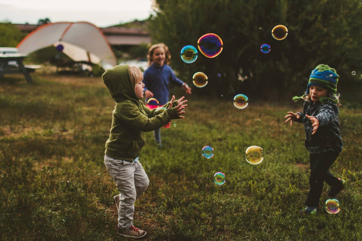 Children pay outdoors whilst chasing bubbles.
