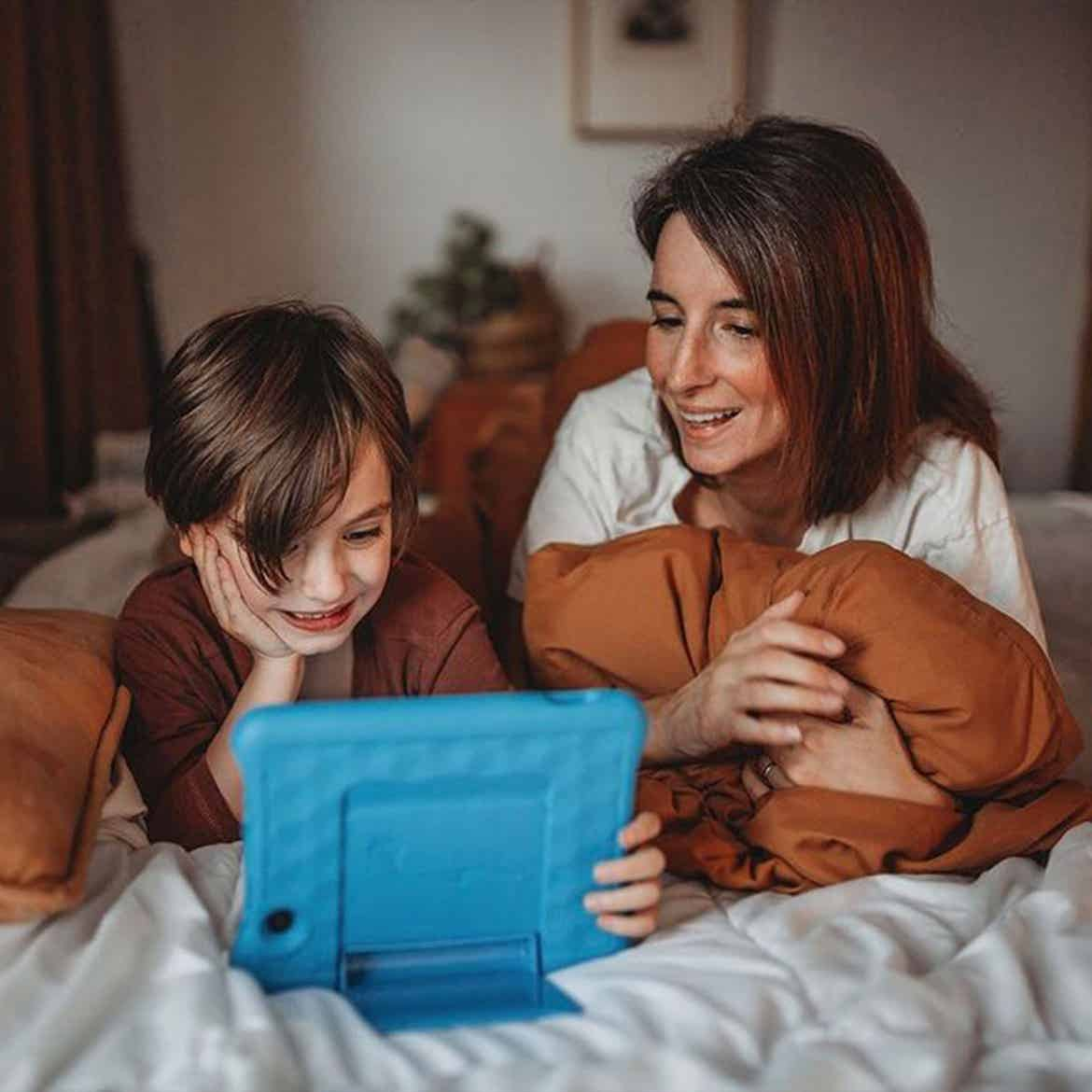 Featured Contributor, Eileen Lamb's son sits alongside her watching a tablet.