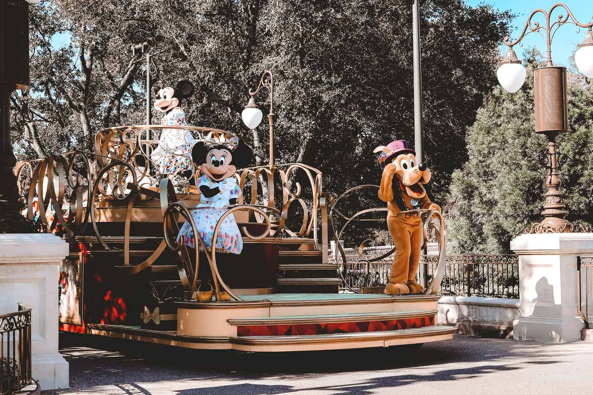 Mickey (back-left), Minnie (front-left) and Pluto (front-right) ride a parade float at Magic Kingdom Park at Walt Disney World® Resort wearing their Birthday Party outfits.