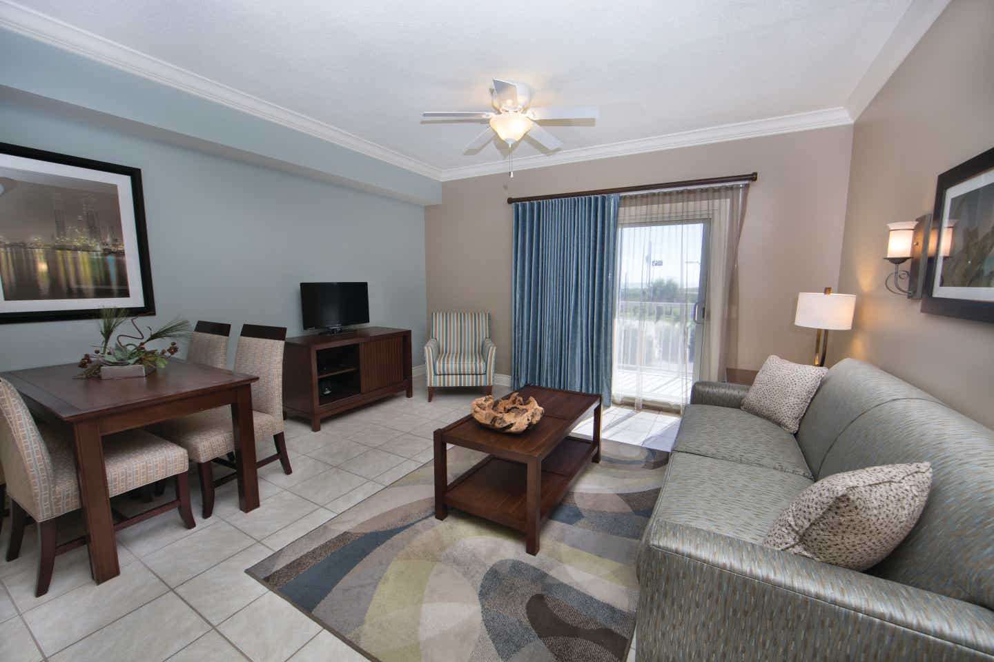 Living room with couch, flat screen TV, and access to balcony