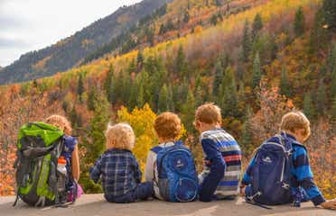 Jessica's kids sitting on the edge of a rock in front of gorgeous fall foliage and mountainous landscapes