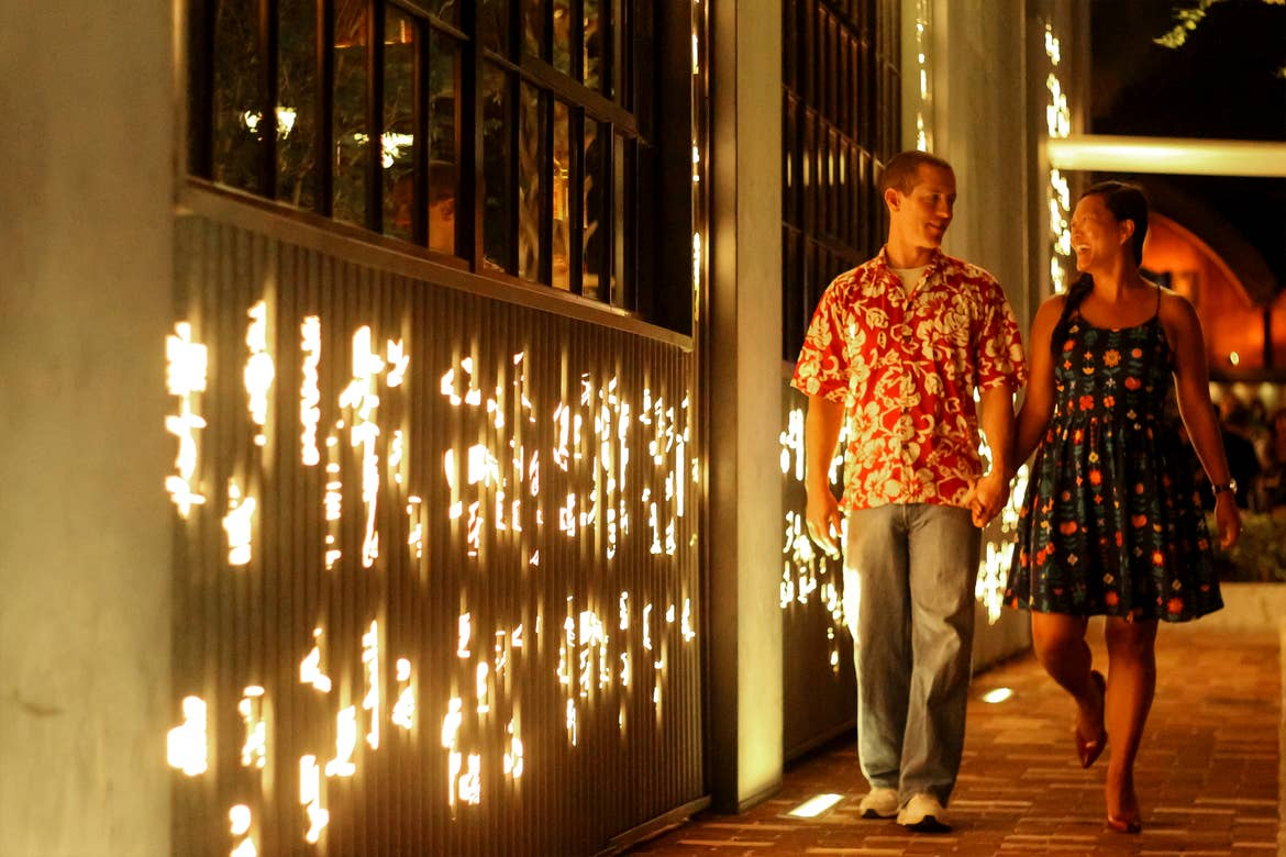 A Caucasian man wearing a red Hawaiian shirt and jeans (left) walks with an Asian woman wearing a patterned, navy dress (right) as they walk next to a building exterior with die-cut lights at night.