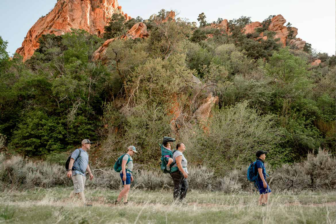 Featured Contributor, Melody Forsyth (middle-right), and her family walk single-file in front of a rock formation while wearing hiking backpacks.