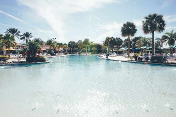 Outdoor pool with beach chairs surrounded by palm trees in West Village at Orange Lake Resort near Orlando, Florida