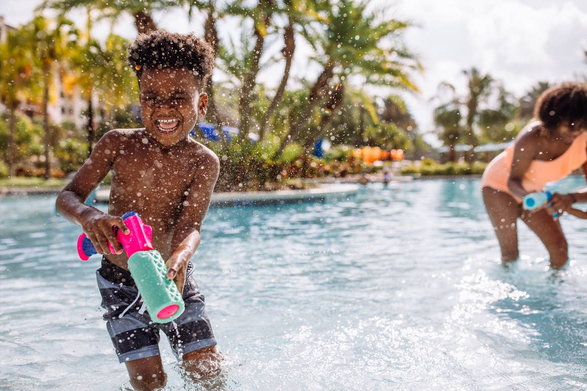 Krystin Godfrey's son, Joshua (left) gets splashed by Sabria's (right) squirt gun in the pool.