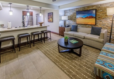 Living room with decorative stone wall and couch in a signature one-bedroom villa at Scottsdale Resort