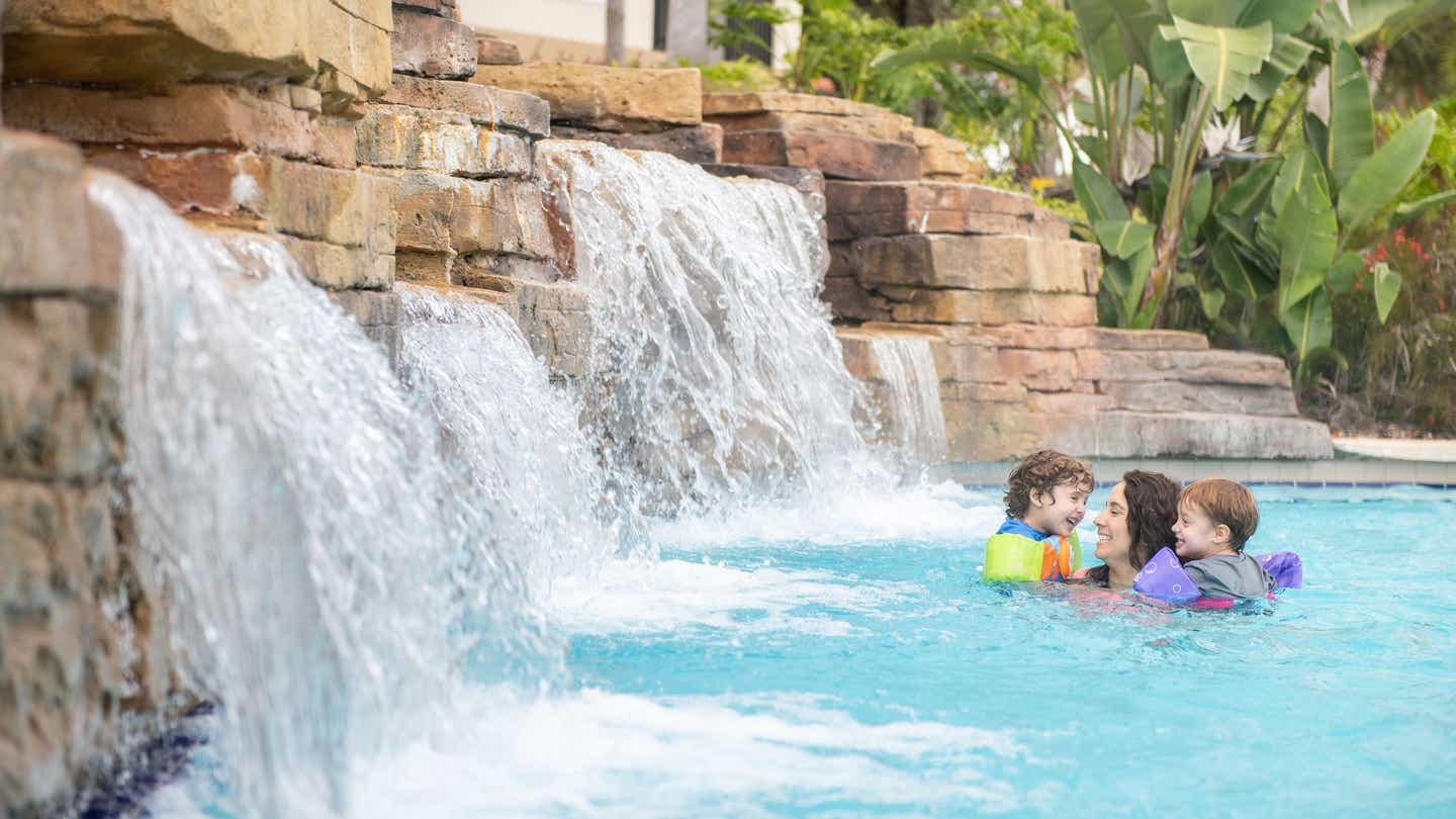Mother and her two sons playing near a waterfall in the pool at Orange Lake Resort in Orlando, FL