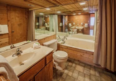 Bathroom in a one-bedroom log cabin at Holly Lake Resort in Holly Lake Ranch, Texas.