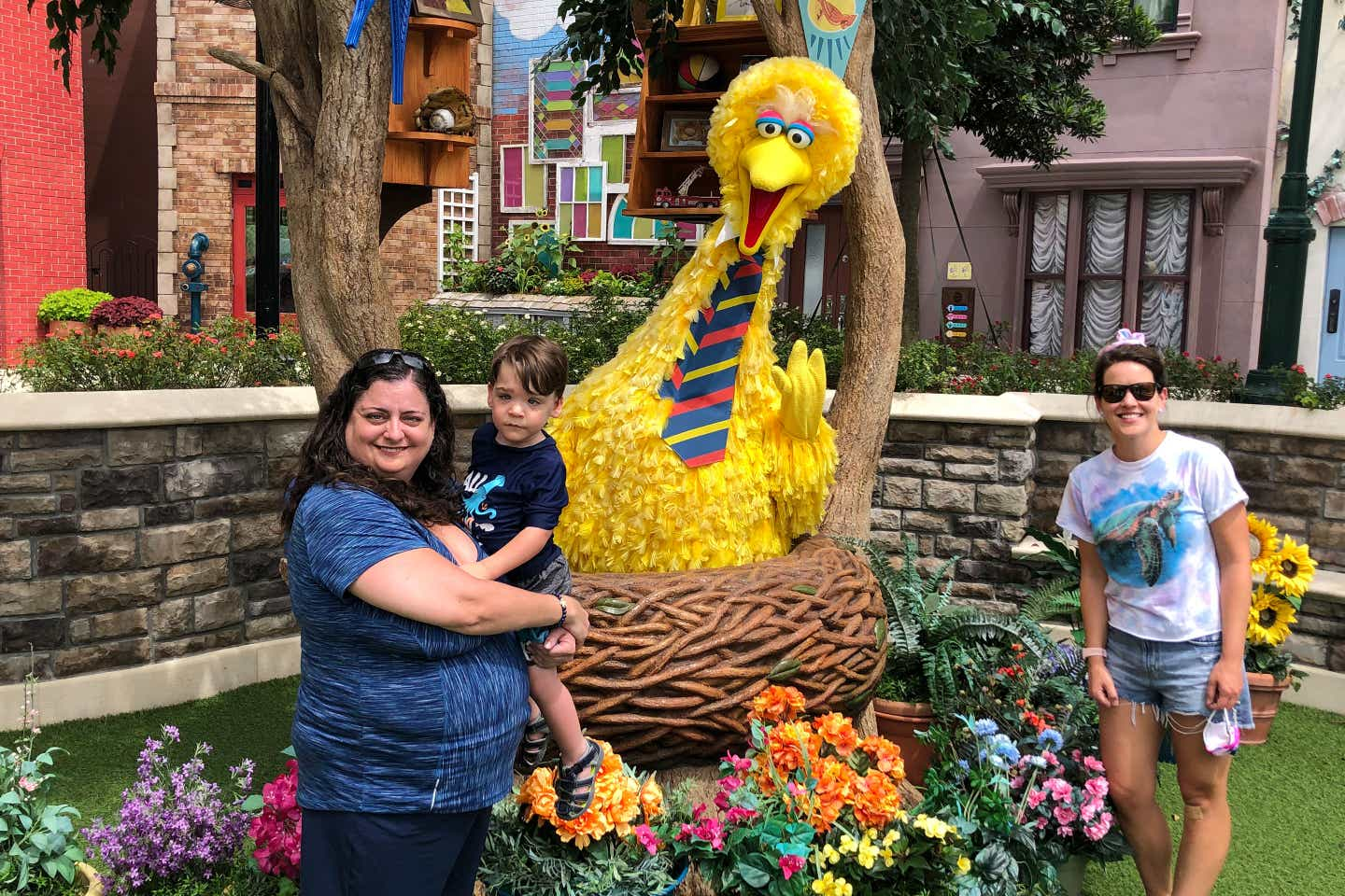 Theresa holds Dakota (left) with Jennifer (right) in front of Big Bird in his nest for a photo.