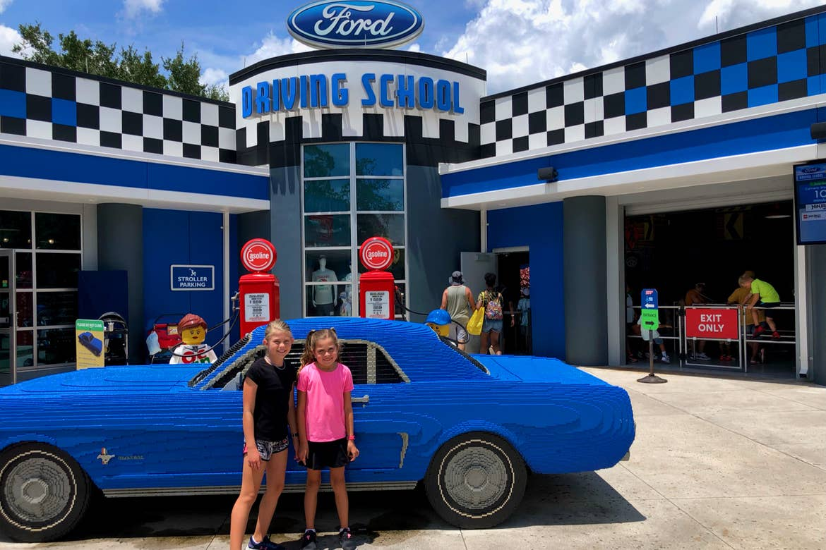Two young girls stand in front of an auto shop and vintage car made entirely of LEGOS.