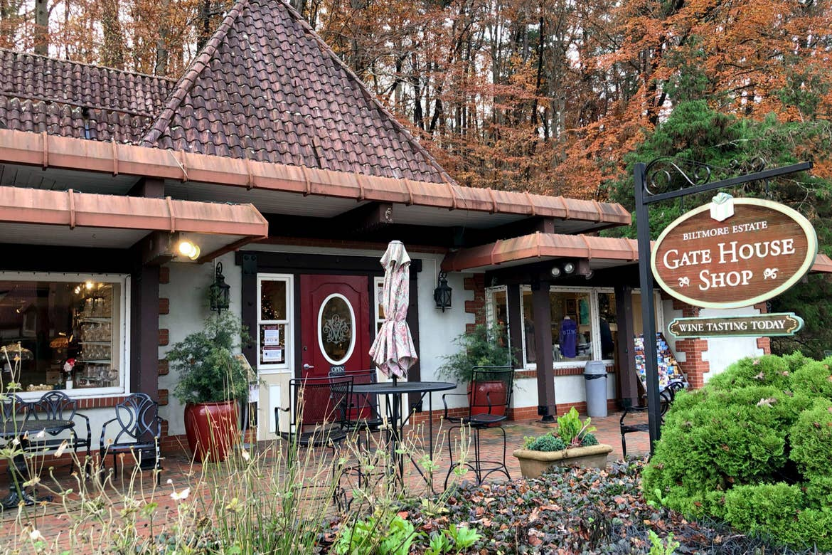 The exterior of a Gate House Shop near the Biltmore Estate with signage that reads, 'Biltmore Estate, Gate House Shop, Wine Tasting Today.'
