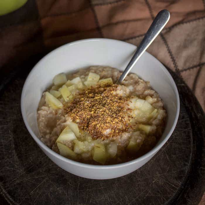 A shot of oatmeal sitting on a table topped with cinnamon, graham cracker crust and apple slices.