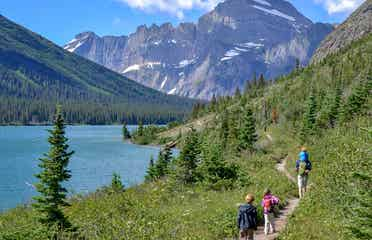 Featured Contributor, Jessica Averett's family walk a trail near Glacier Lake at Glacier National Park.