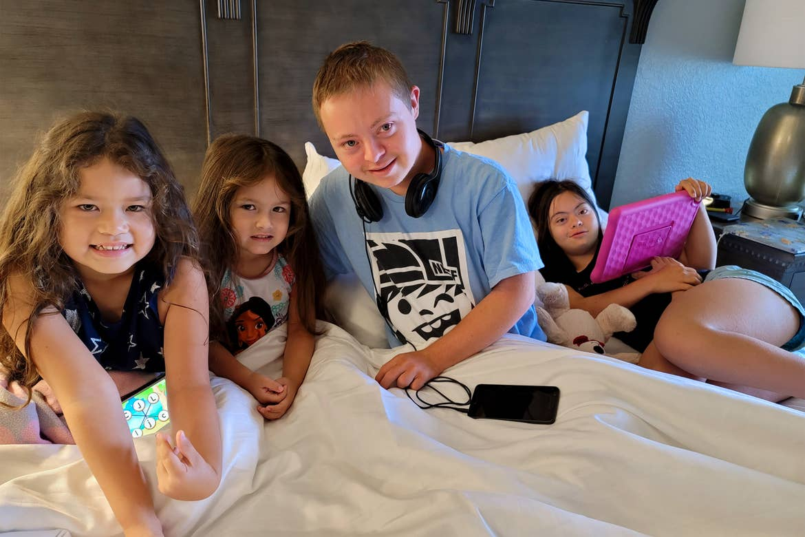 From Left to Right: Two young girls, a young boy, and another young girl holding a pink iPad sit on a large bed.