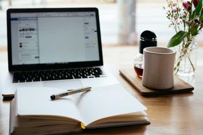 A laptop sits alongside an open notebook, coffee mug and a window.
