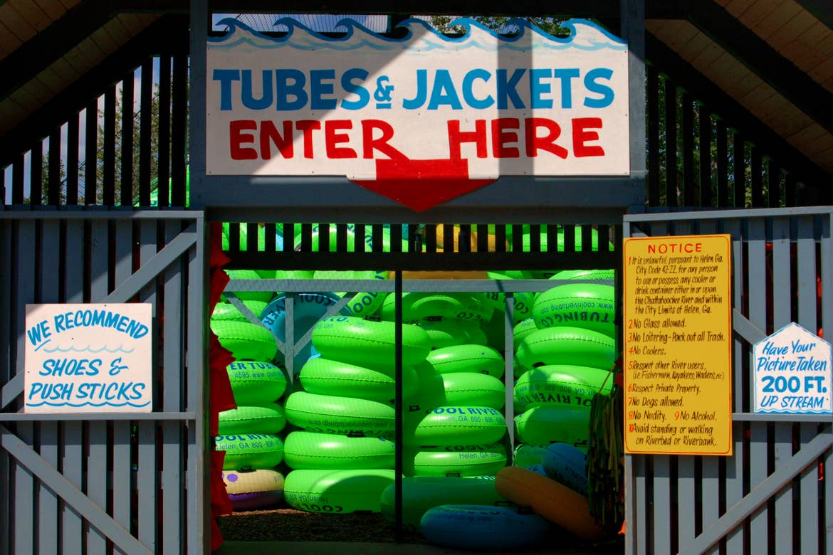 Stacks of bright green inner tubes are placed behind netting near a shack entrance with signage that reads, 'Tube & Jackets, Enter Here'.