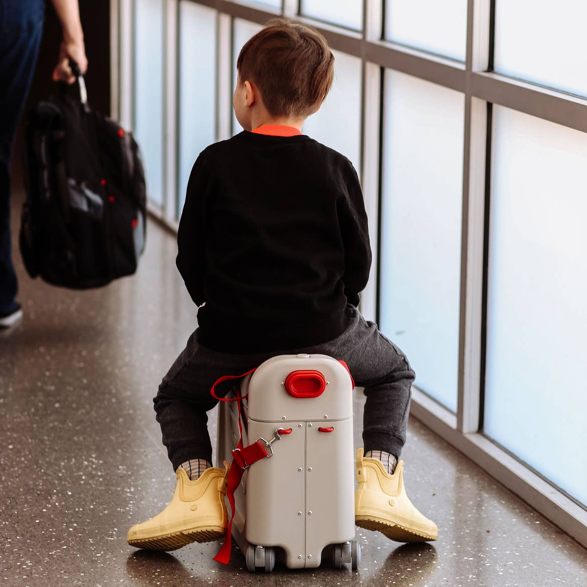 Featured contributor, Mia St. Clair's son, Grey, sits on his white wheeled suitcase in an airport terminal wearing a black shirt and yellow rain booties.