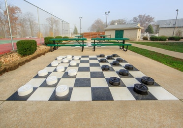 Outdoor giant checkers and nearby benches at Fox River Resort in Sheridan, Illinois