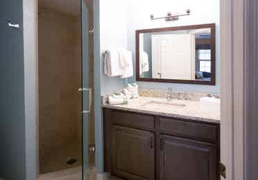Bathroom with sink, large mirror, and walk-in shower in a villa in North Village at Orange Lake Resort near Orlando, Florida